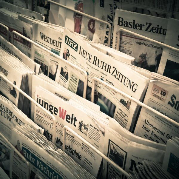 rack of news papers with articles